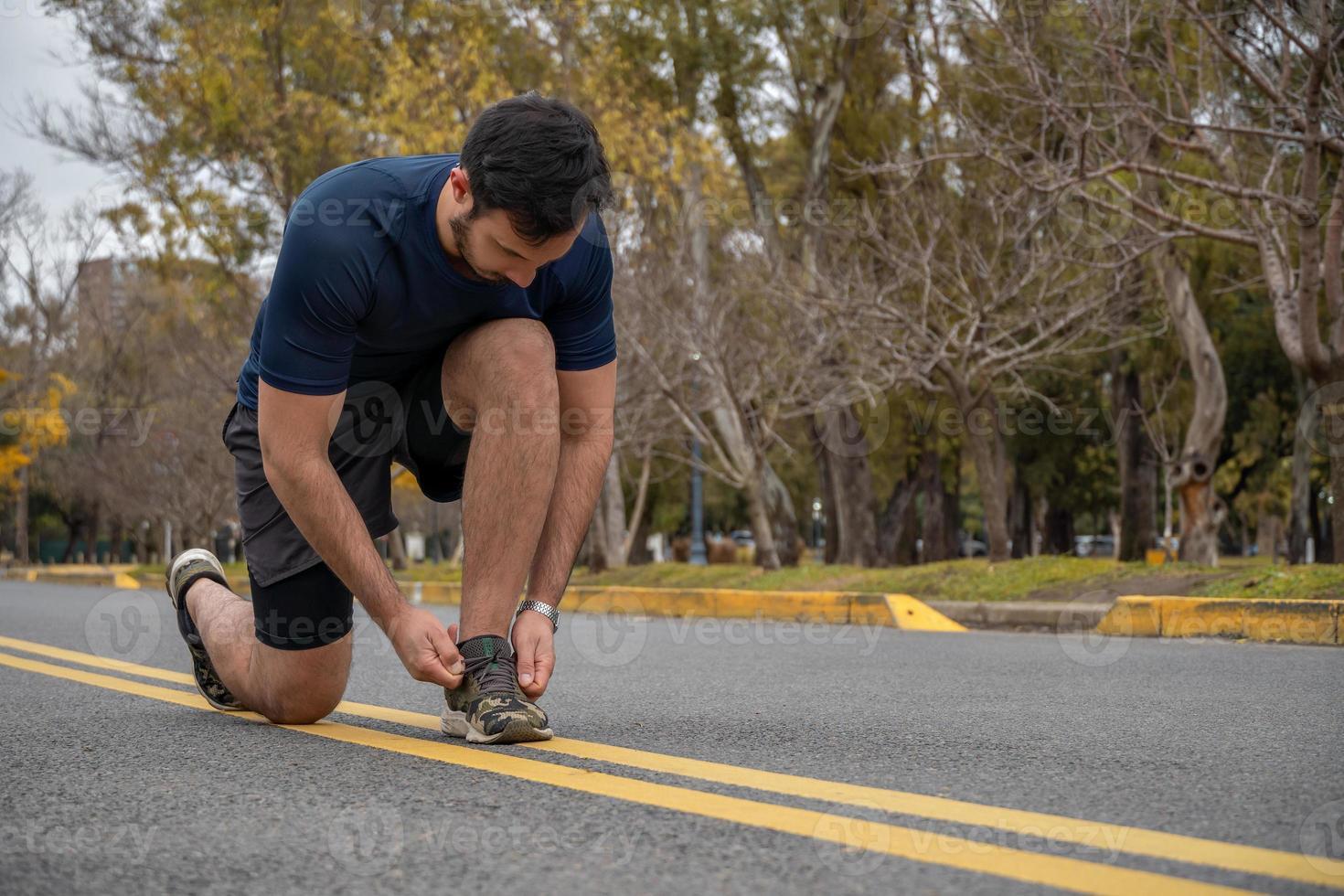 sportlicher Mann, der seine Schnürsenkel bindet, während er im Freien trainiert foto