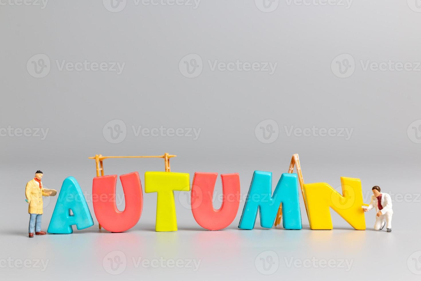 Miniatur-Menschen-Arbeiter-Team-Malerei des Herbstes mit Platz für Text foto