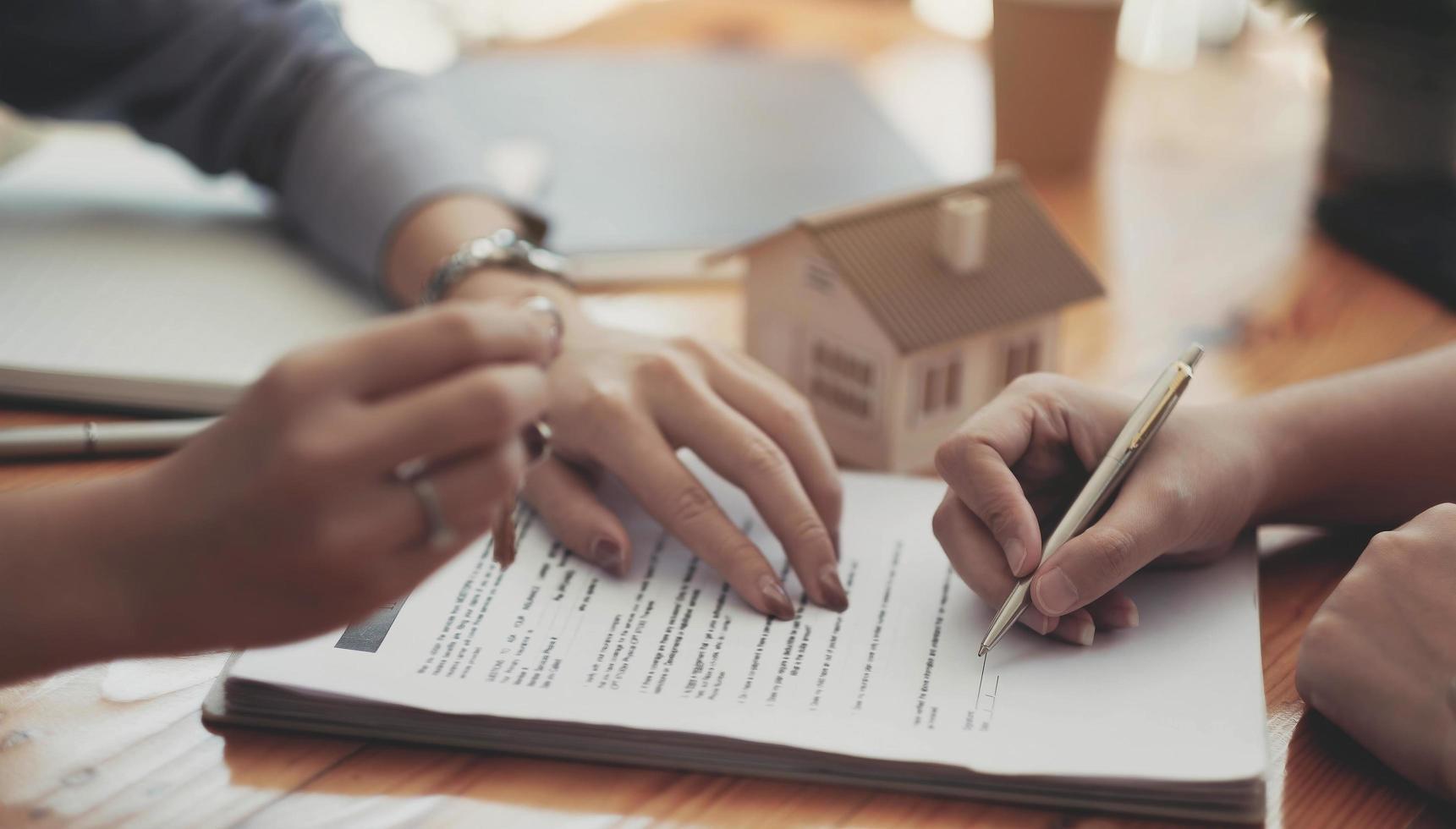 beschnittenes Bild eines Immobilienmaklers, der dem Kunden bei der Vertragsunterzeichnung hilft foto