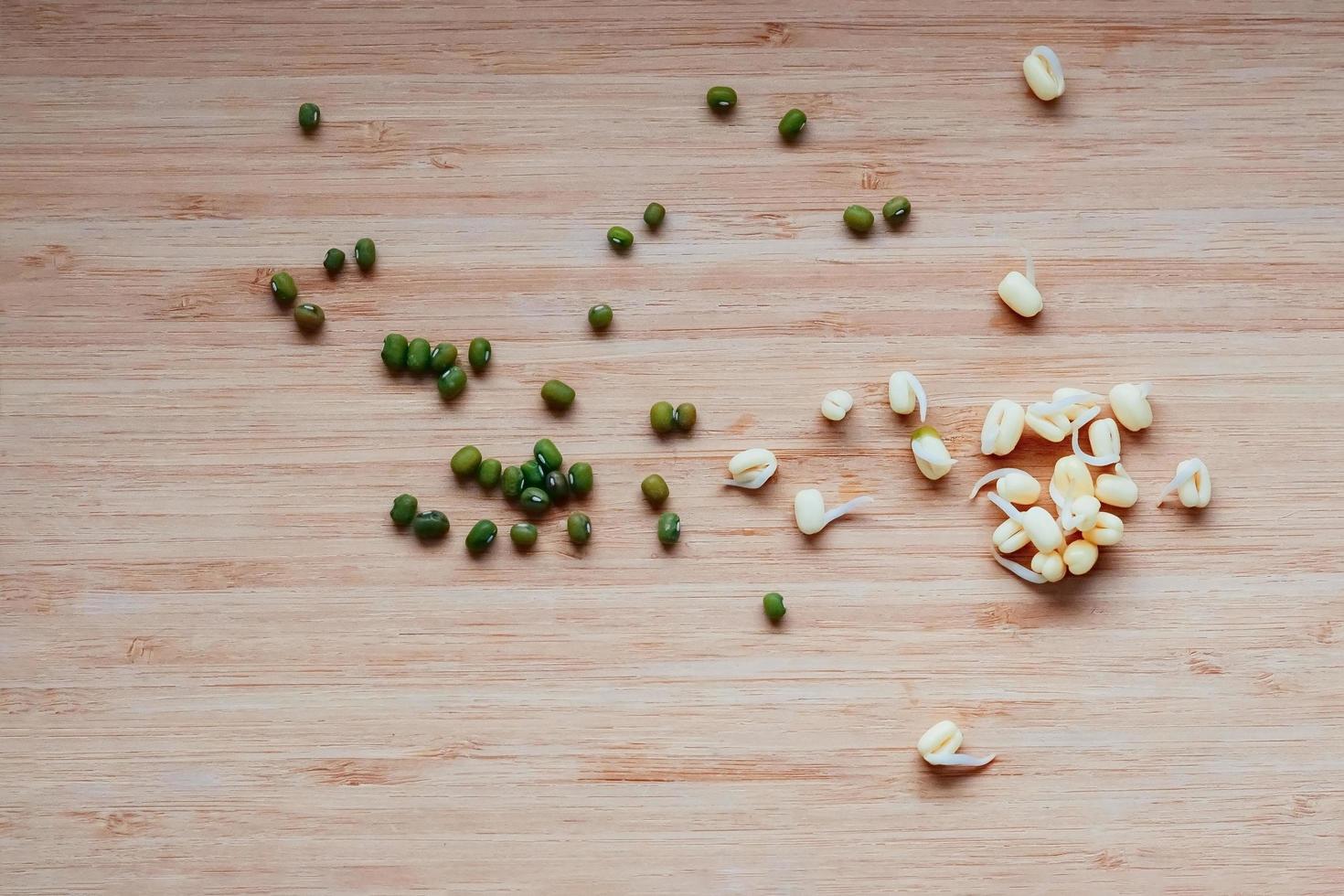 Mungobohnen und ihre Sprossen auf Tisch, Ansicht von oben foto