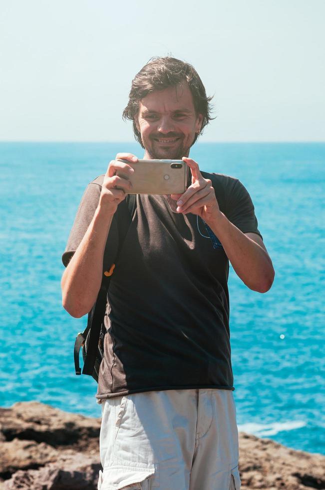 lächelnder glücklicher Mann, der ein Foto gegen das blaue Meer macht