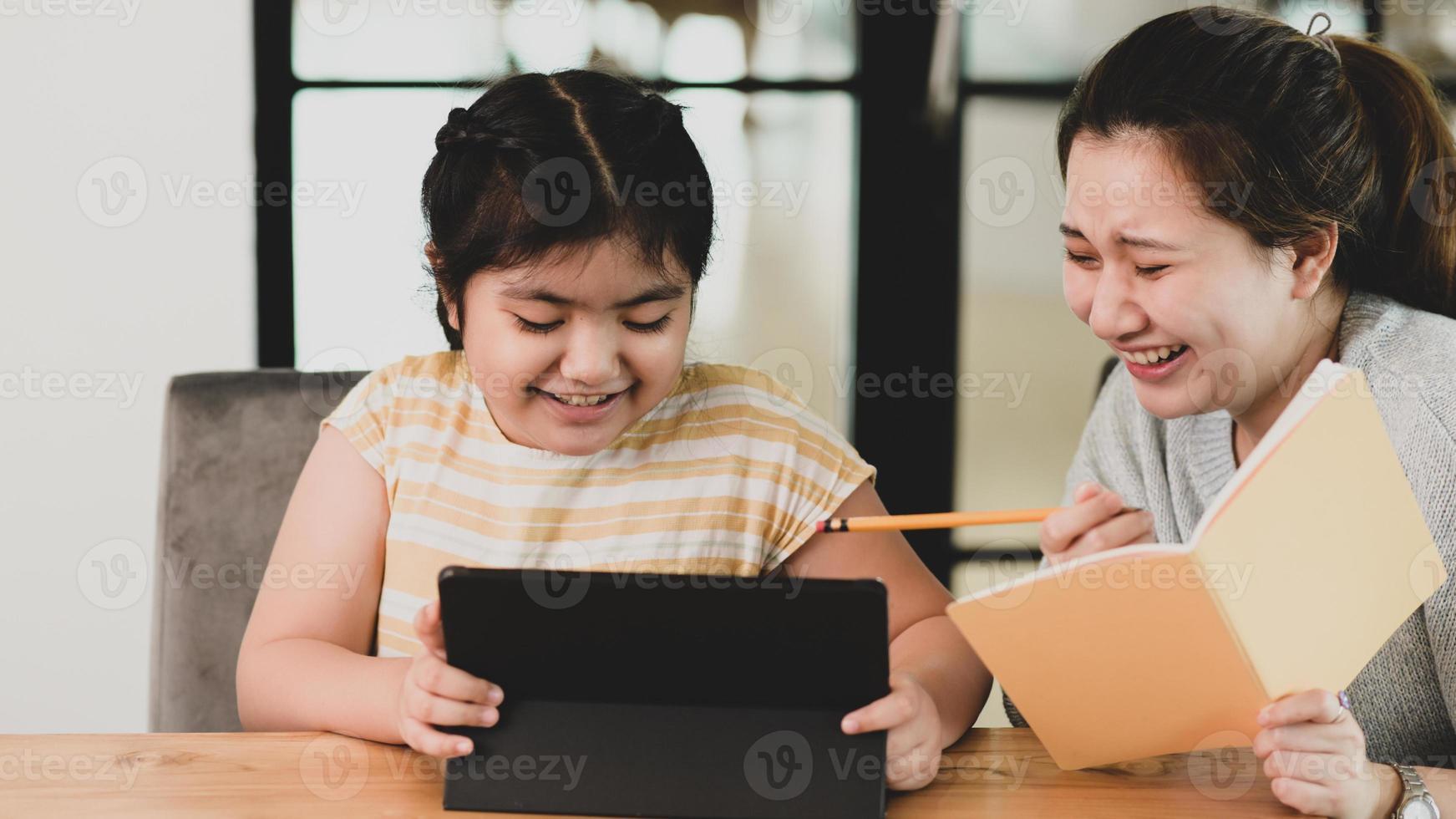 zwei junge asiatische mädchen mit tablet unterrichten ihre hausaufgaben. foto