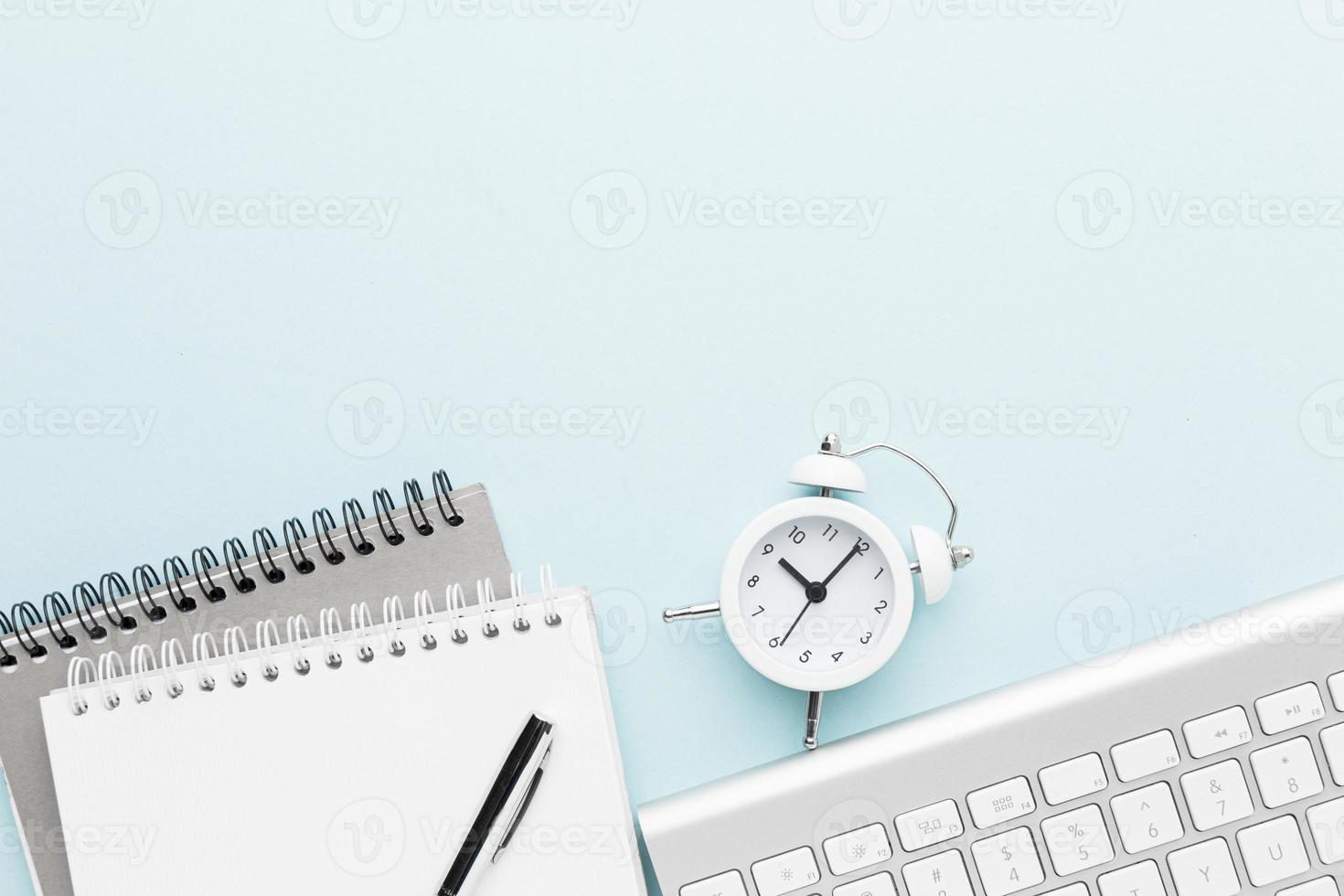 Draufsicht auf ein Notebook und eine Uhr foto