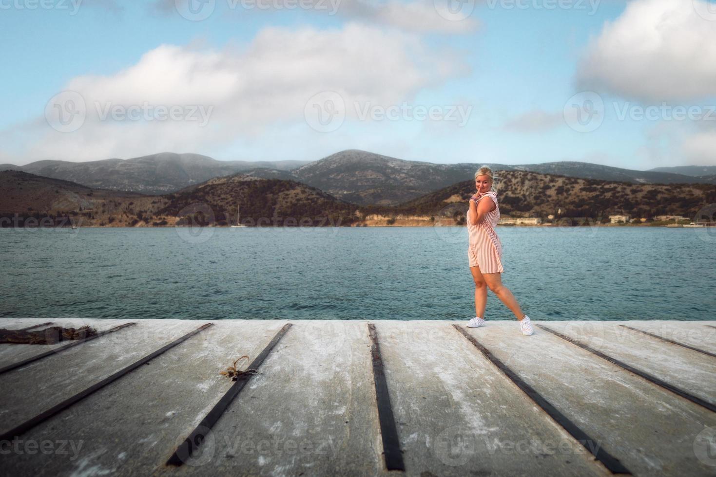 blonde Frau im weißen Kleid mit roten Streifen, die bei Sonnenuntergang auf dem Schiffsdock steht, lächelt und in die Kamera schaut. Tourismuskonzept. Argostoli, Kefalonia, Griechenland. foto