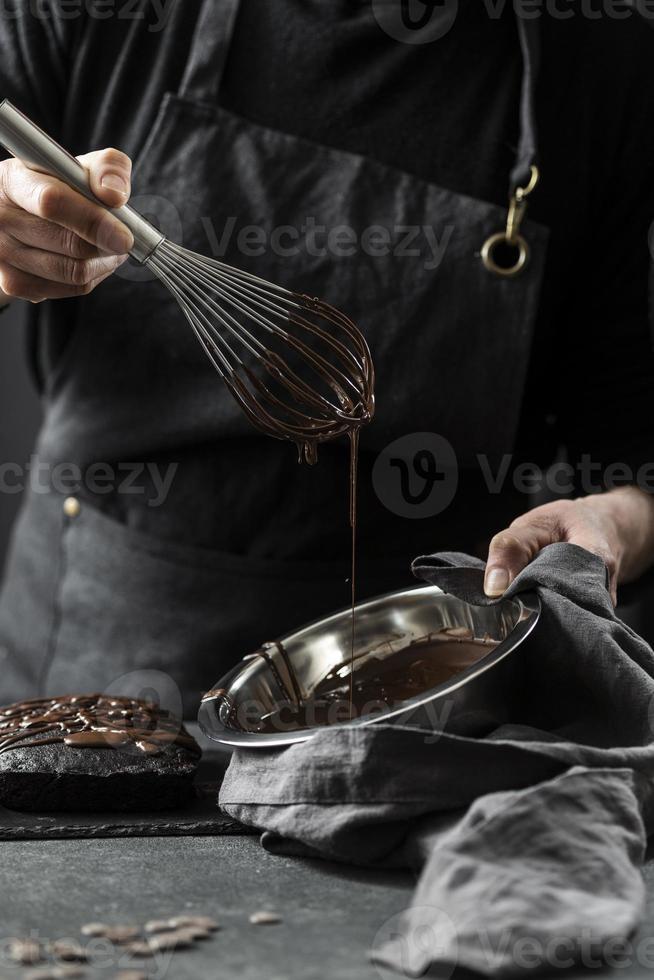 Konditor bereitet Schokoladenkuchen zu foto