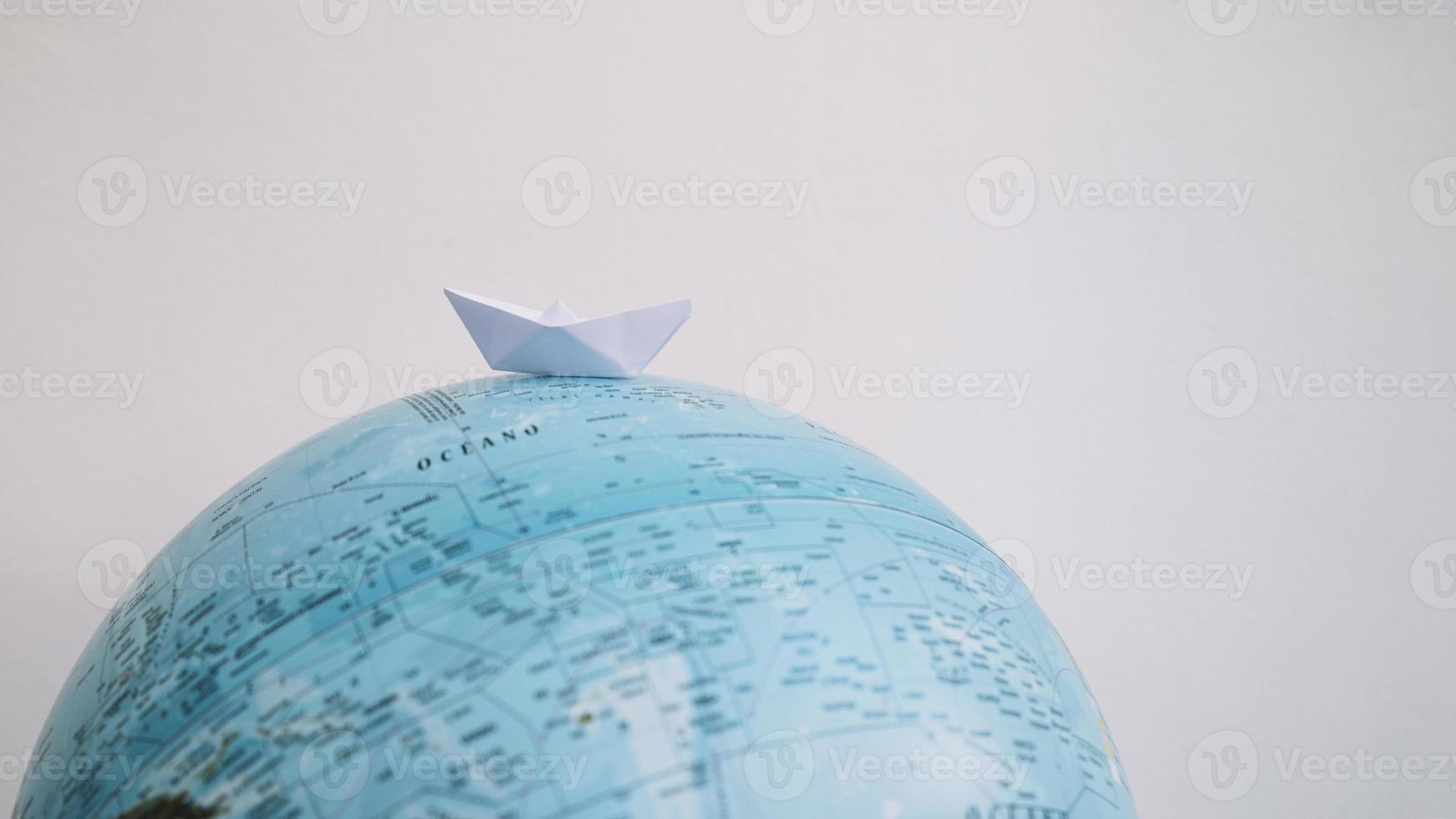 Papierboot auf einem Globus foto