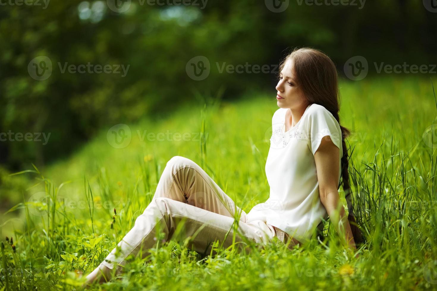 nachdenkliche frau, die auf dem gras sitzt foto