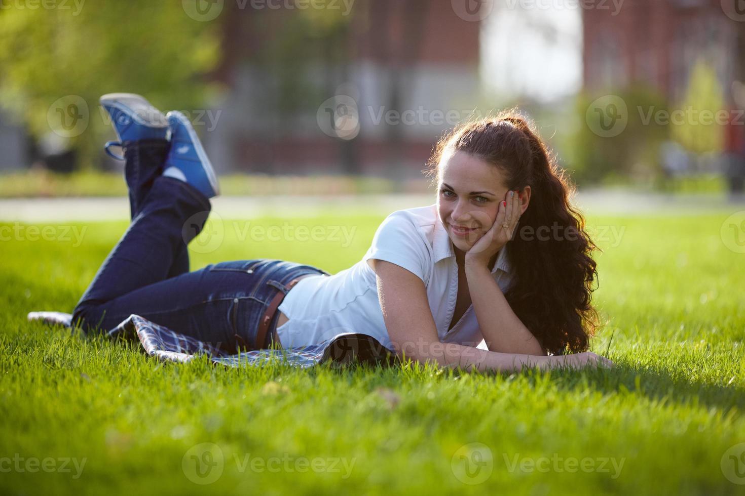 junge Frau liegt auf einer Wiese foto