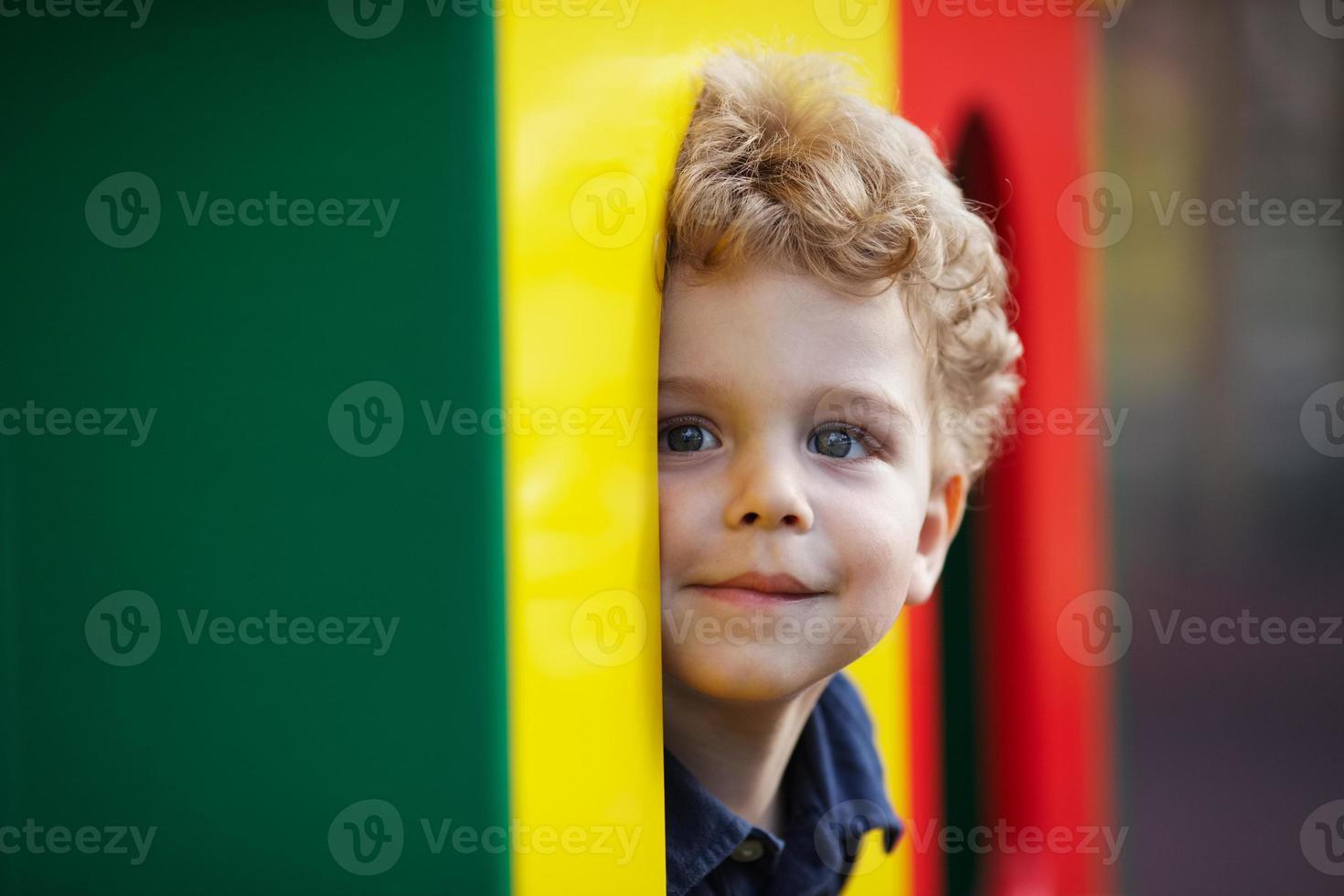 kleiner Junge lugt hinter Deckung hervor foto