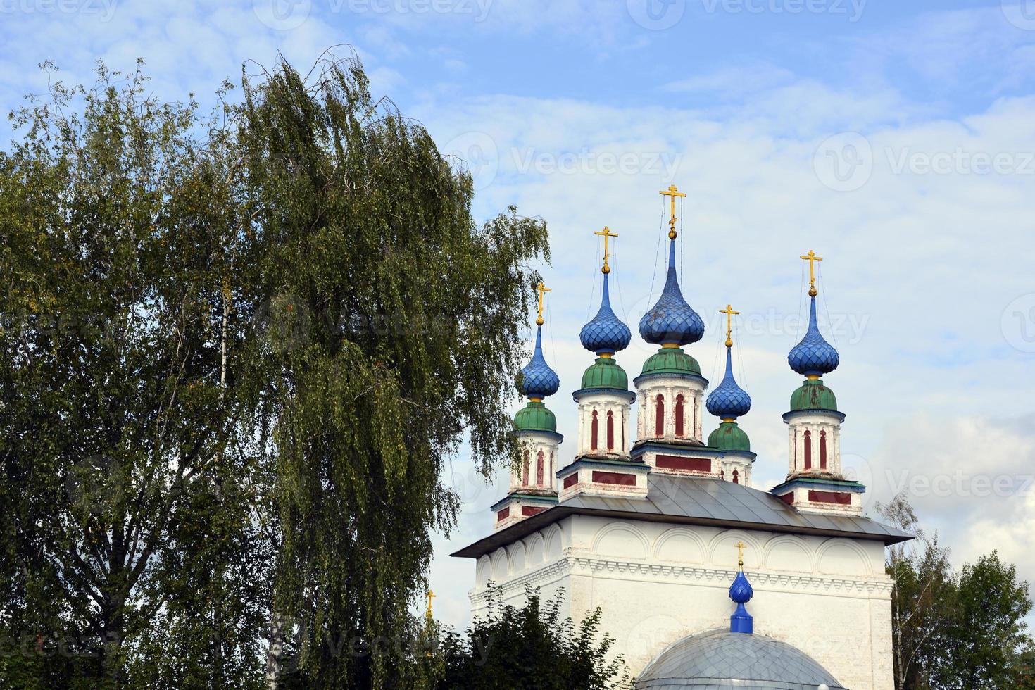 Kirchenkuppeln mit Kreuzen gegen den blauen Himmel. Tempel aus weißem Stein im russischen Dorf. foto