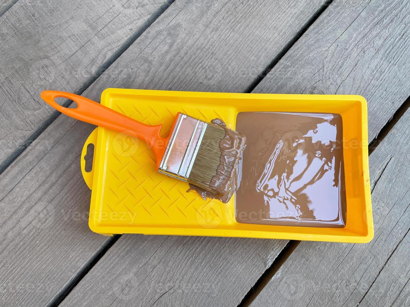 gelbes Tablett mit grüner Farbe mit Pinsel auf Holzuntergrund foto