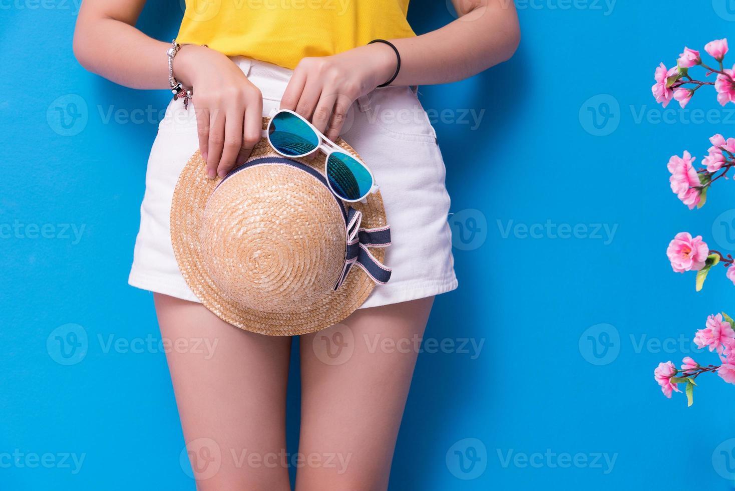 Nahaufnahme der Schönheitsfrau, die mit Sonnenbrille und Strohhut vor blauem Wandhintergrund aufwirft. Sommer- und Vintage-Konzept. Glück Lifestyle und Menschen Portrait Thema. süßer Pastellton. Unterkörper foto