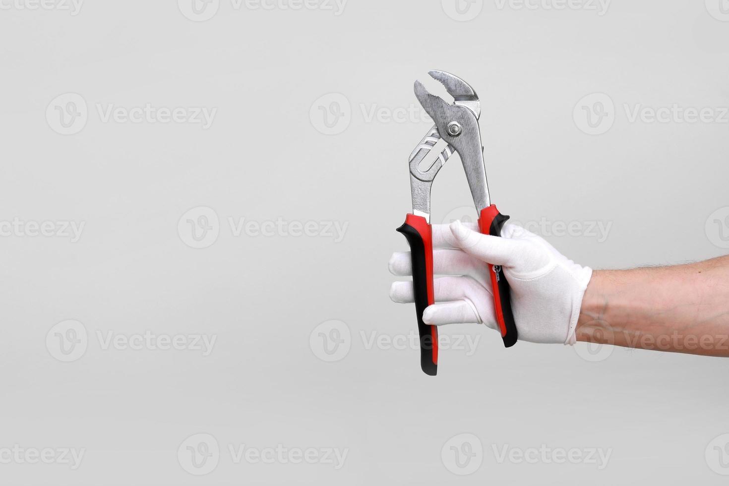 Mans Hand in weißem Handschuh angehoben hält eine schwarze und rote Werkzeugzange, Drahtschneider. isoliert auf weißem Hintergrund. offene, saubere, schneidfertige Form. Kopienraum modellieren foto