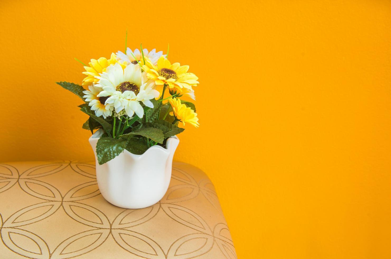 Strauß gelber Gänseblümchen in weißer Vase foto