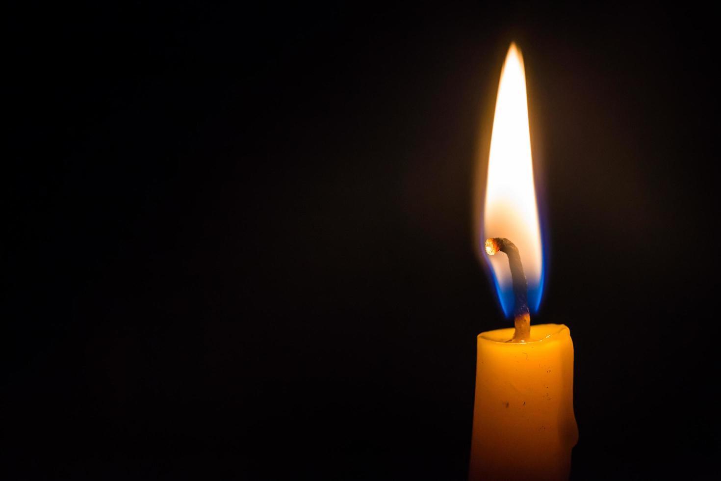 Nahaufnahme helle Kerze, die hell im schwarzen Hintergrund brennt. foto