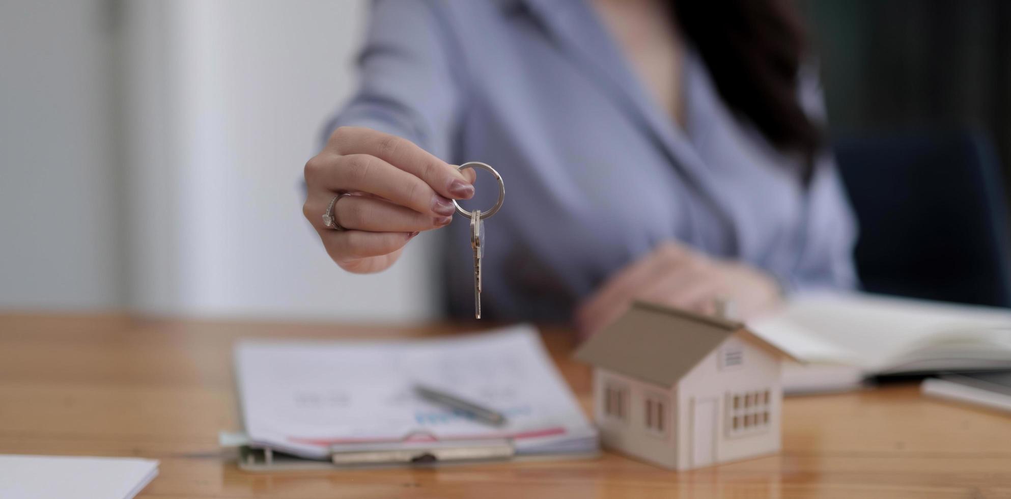 Hausschlüssel im Handschutz des Hausversicherungsmaklers oder in der Verkäuferperson, die dem Käufer des Kundenbesitzers übergibt foto