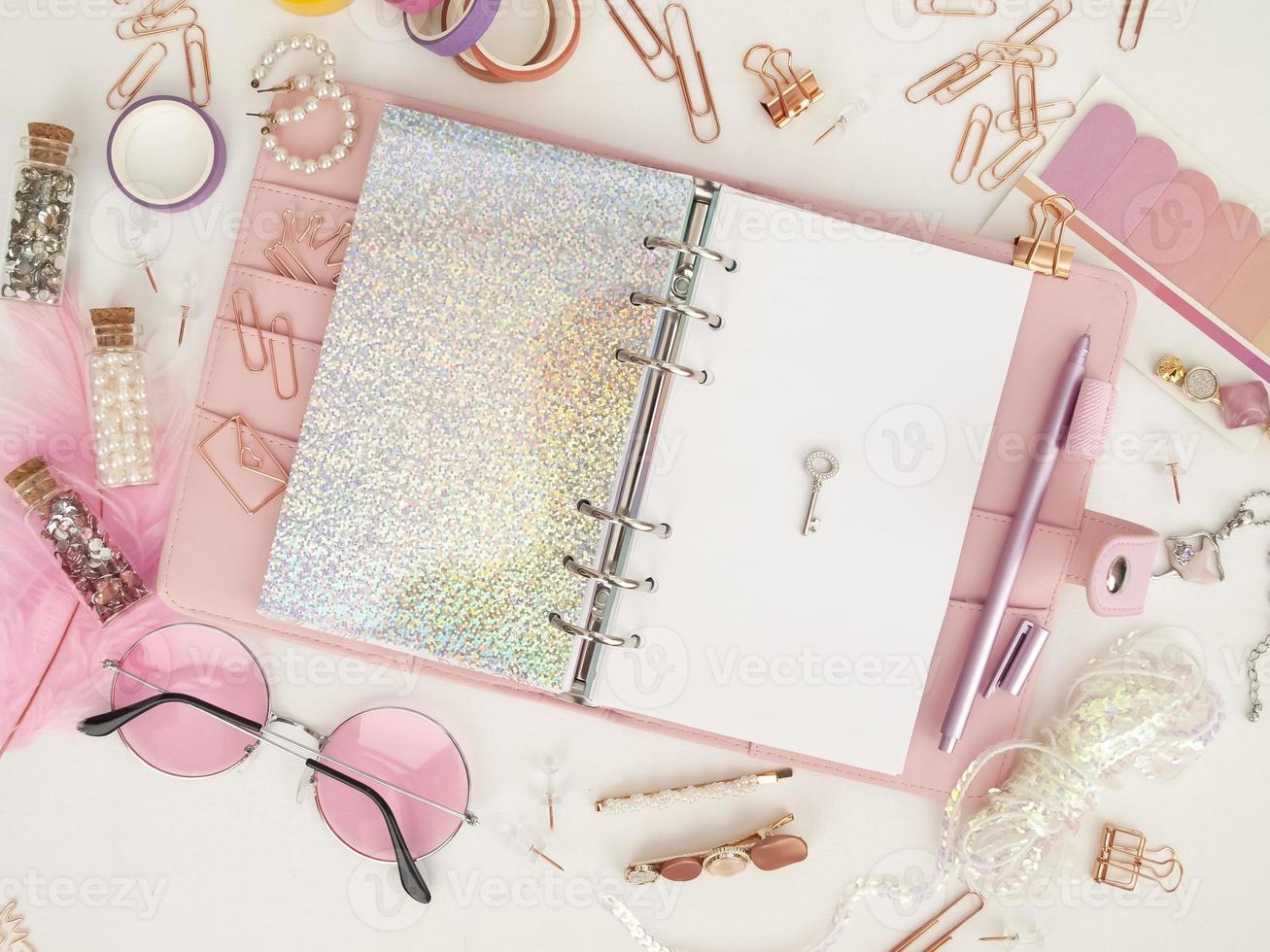 silberner Schlüssel auf der weißen Seite des Planers. Tagebuch offen mit weißer und holografischer Seite. Draufsicht auf den rosa Planer mit Briefpapier. rosa Glamour-Planer Dekorationsfoto foto