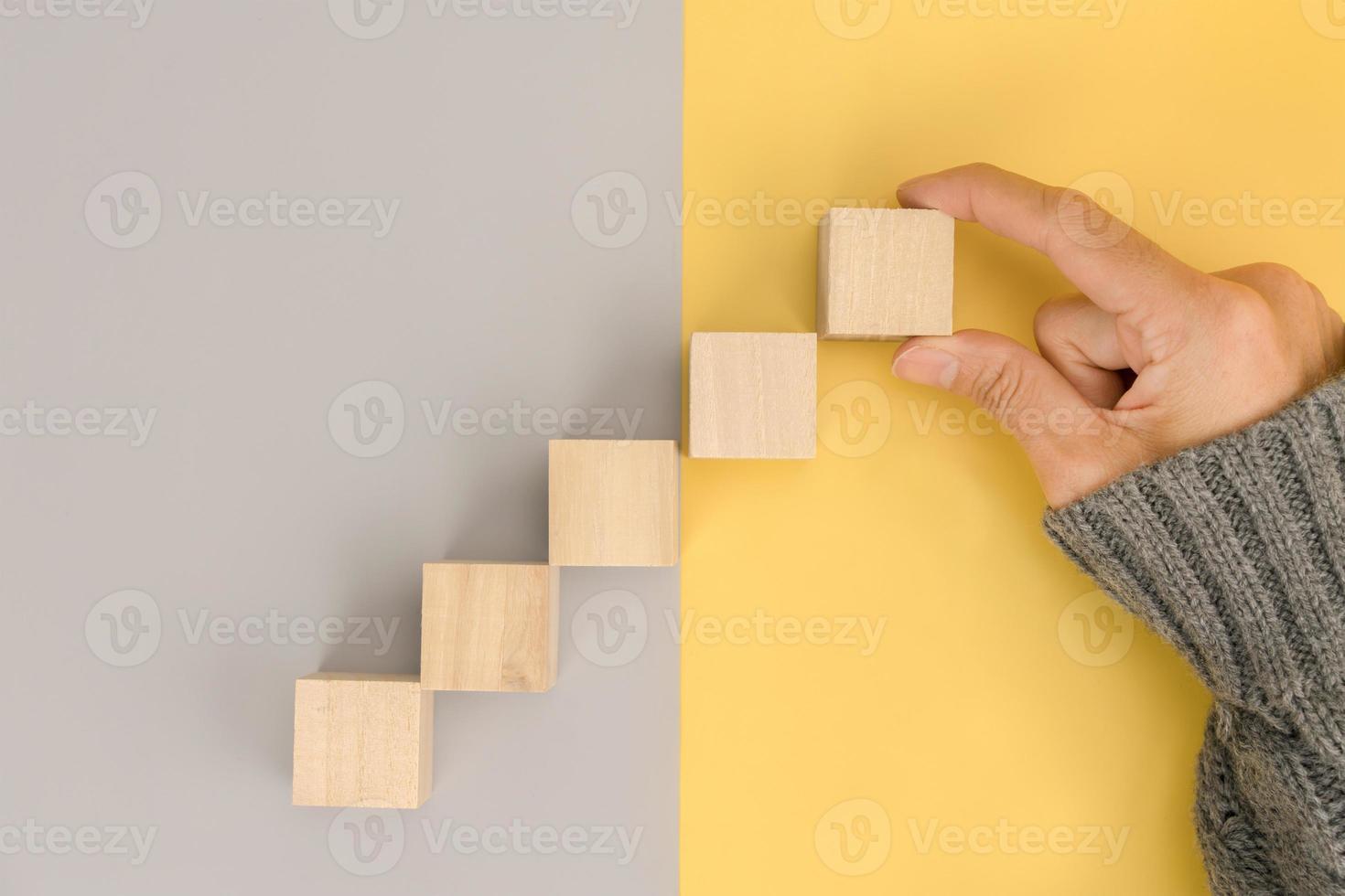 Frauenhand, die leeren Holzblock anordnet und Platz auf grauem und gelbem Hintergrund kopiert foto