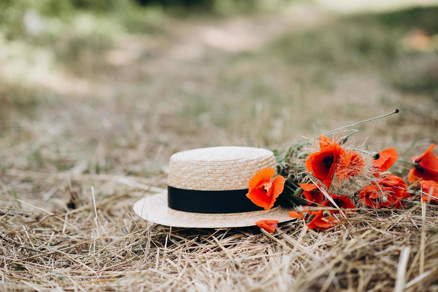 Strauß Mohnblumen mit einem Leinenhut auf einem goldenen trockenen Strohhalm. Platz zum Einfügen von Text. Sommer Konzept. foto