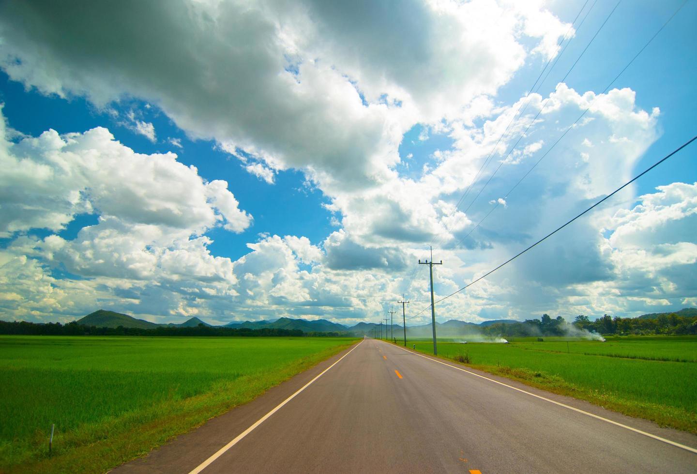 Asphaltstraße durch die grüne Wiese und Wolken am blauen Himmel im Sommer foto
