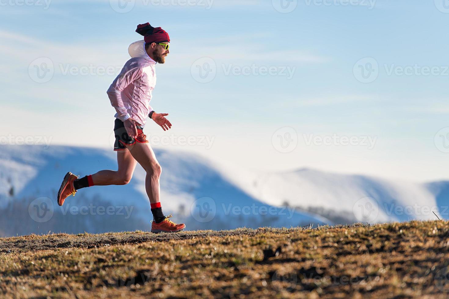 Bergrennen. Training eines Sportlers zwischen Wiese und Schnee foto