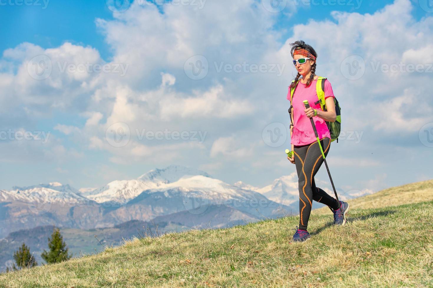 Spaziergang auf den frühlingshaften Bergwiesen mit schneebedeckten Bergen im Hintergrund foto