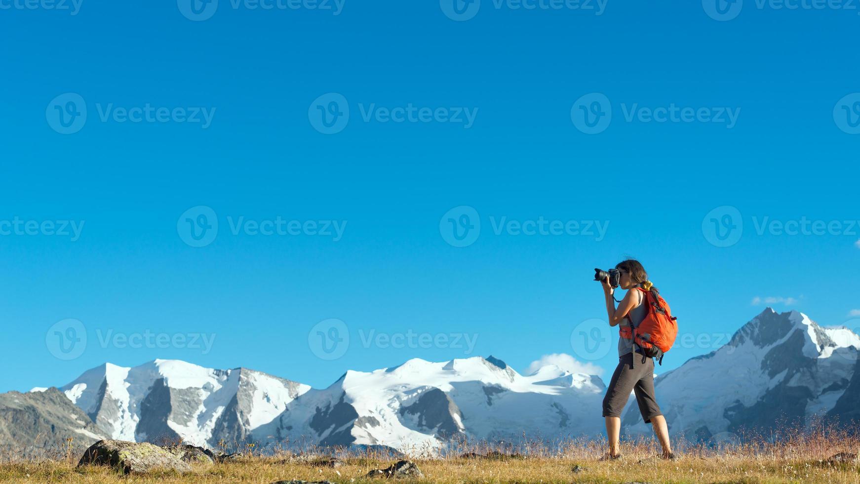 Mädchen fotografiert hohe Berge der Alpen foto
