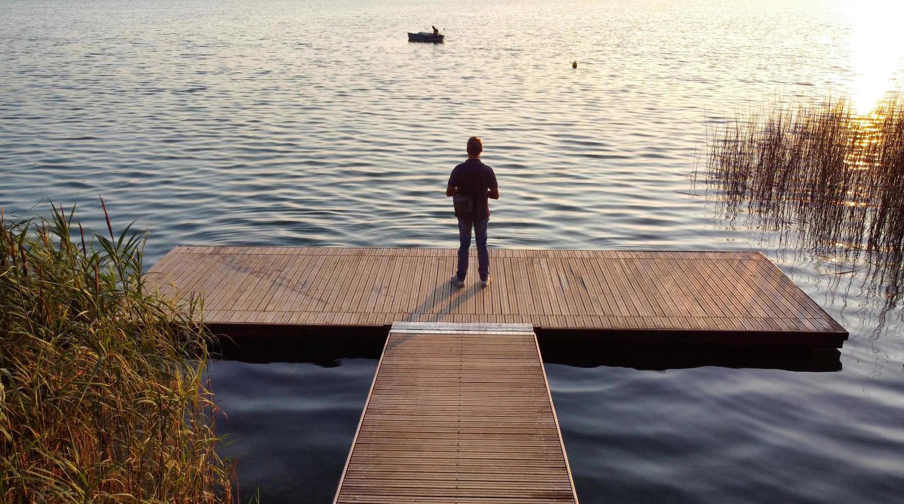 Mann steht auf einem Holzsteg foto