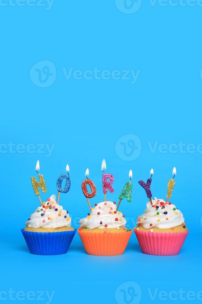 Cupcakes mit Kerzen, die Hurra sagen foto