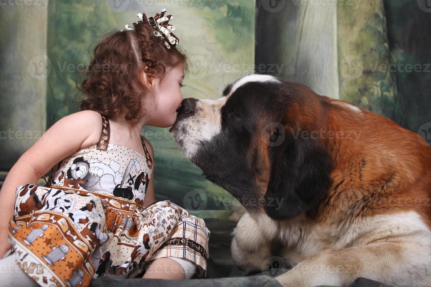 entzückendes Kind und ihr Bernhardiner-Hündchen foto