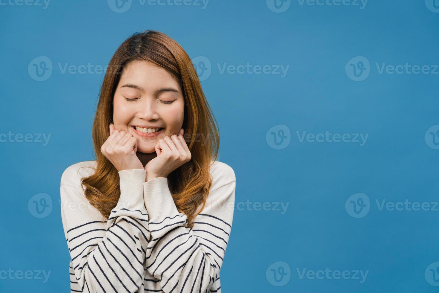 junge asiatische dame mit positivem ausdruck, breit lächeln, legere kleidung tragen und die augen vor blauem hintergrund schließen. glückliche entzückende frohe frau freut sich über erfolg. Gesichtsausdruck Konzept. foto