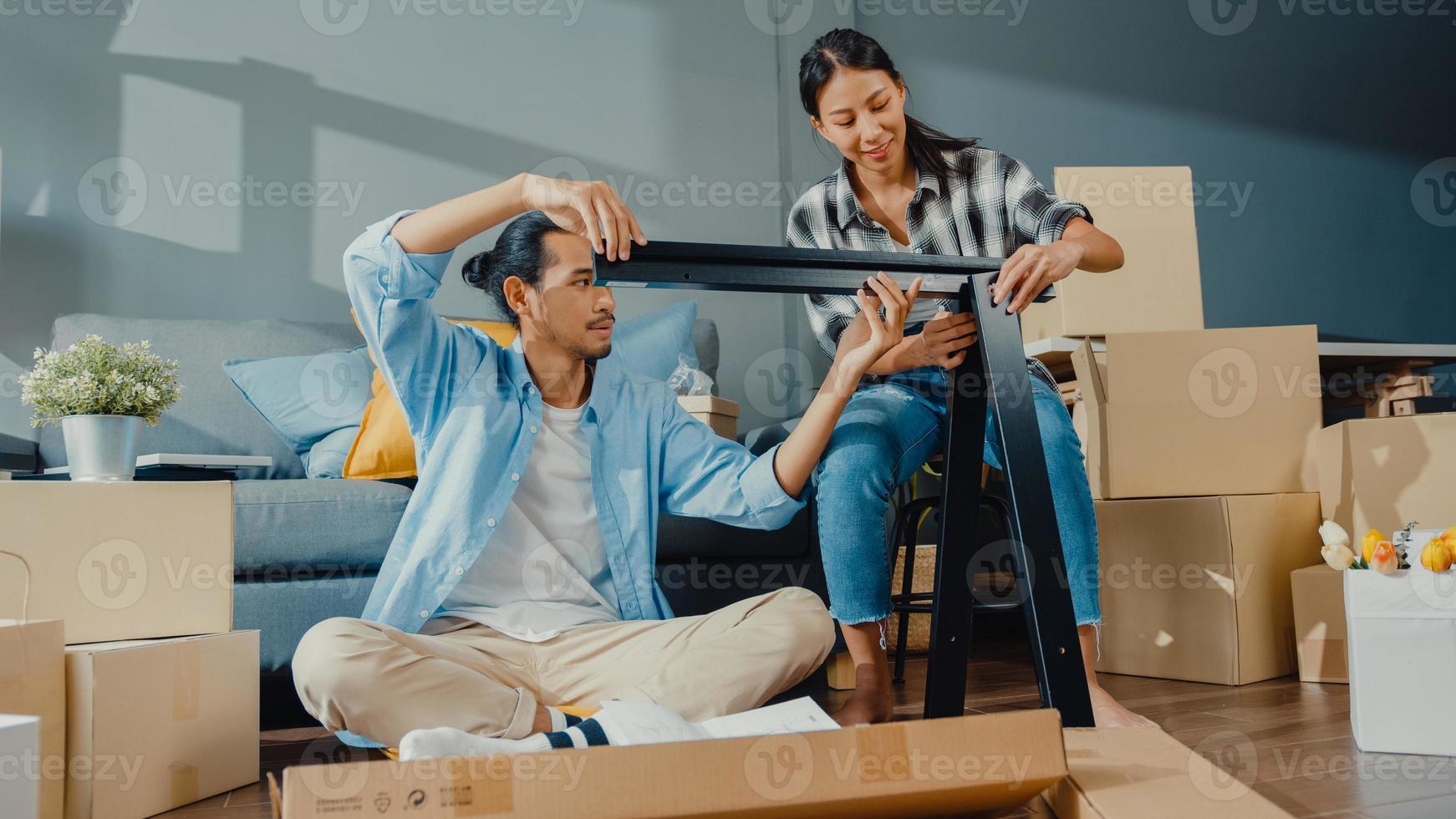glückliche asiatische junge attraktive paar mann und frau helfen sich gegenseitig beim auspacken der box und montieren möbel dekorieren hausbautisch mit karton im wohnzimmer. Junges verheiratetes asiatisches Umzugskonzept. foto