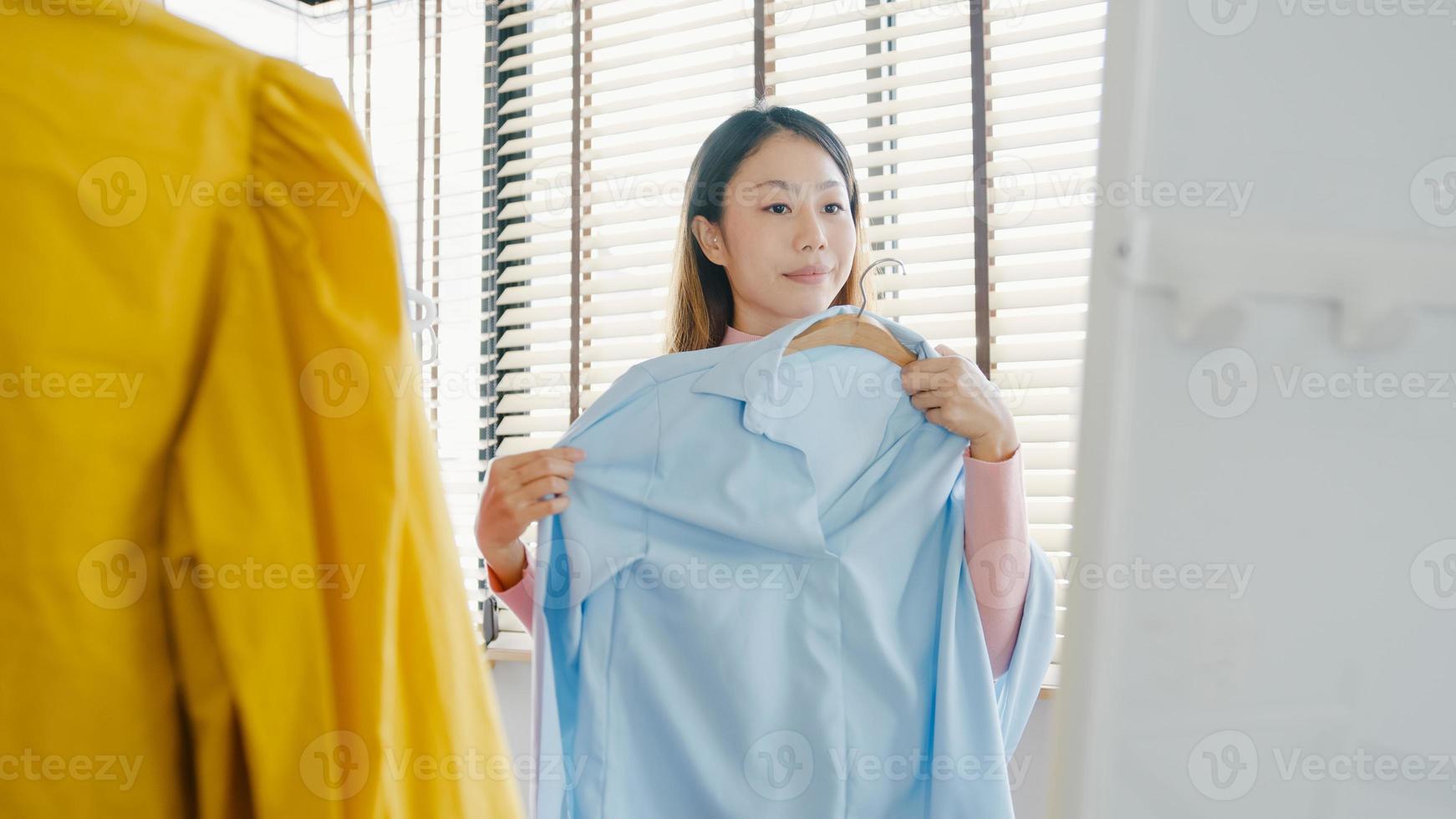 Schöne attraktive asiatische Dame, die Kleidung auf Kleiderständer auswählt, die sich im Spiegel im Schlafzimmer im Haus anzieht. Mädchen denken, was lässiges Hemd zu tragen. Lifestyle-Frauen entspannen sich zu Hause Konzept. foto