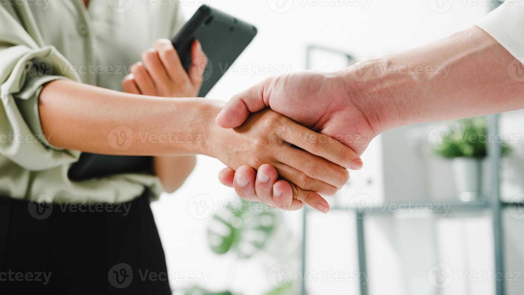 Multirassische Gruppe junger kreativer Menschen in smarter Freizeitkleidung, die über Geschäfte diskutieren, die Hände schütteln und lächeln, während sie in einem modernen Büro stehen. partnerkooperation, mitarbeiterteamwork-konzept. foto