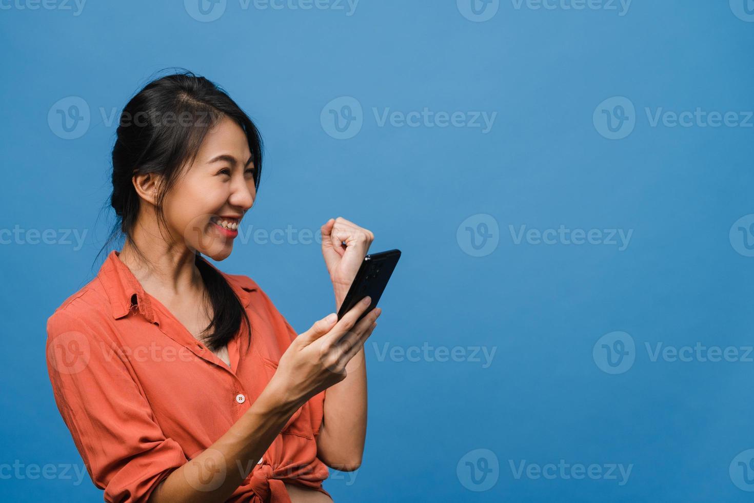überraschte junge asiatische dame, die handy mit positivem ausdruck benutzt, breit lächelt, in lässiger kleidung gekleidet und auf blauem hintergrund isoliert steht. glückliche entzückende frohe frau freut sich über erfolg. foto