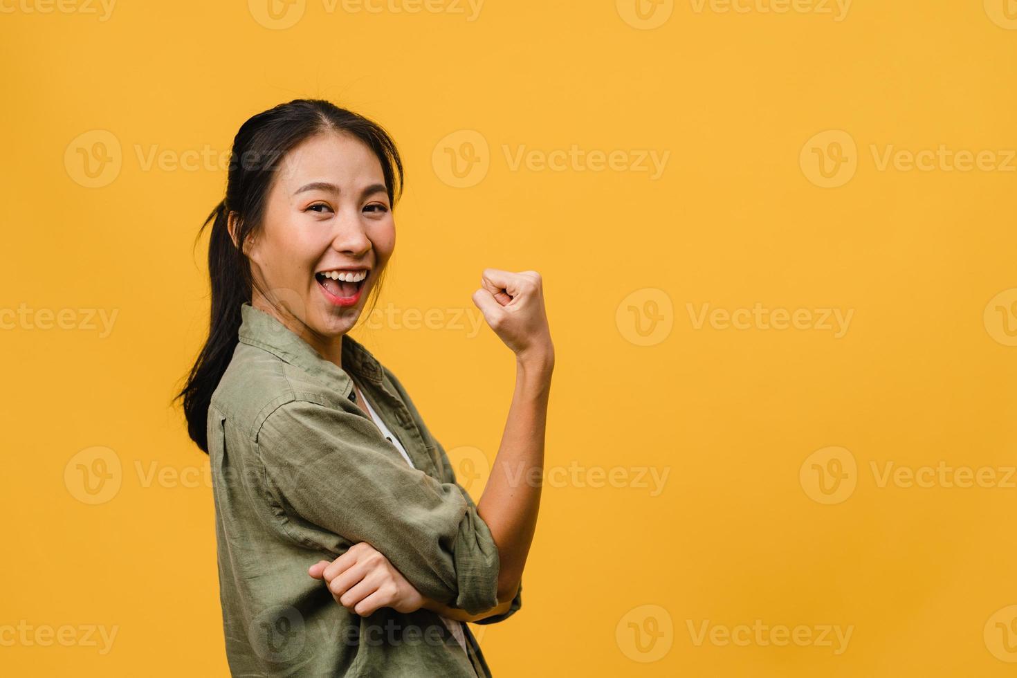 junge asiatische dame mit positivem ausdruck, fröhlich und aufregend, in lässigem tuch gekleidet und blick in die kamera auf gelbem hintergrund. glückliche entzückende frohe frau freut sich über erfolg. Gesichtsausdruck Konzept. foto