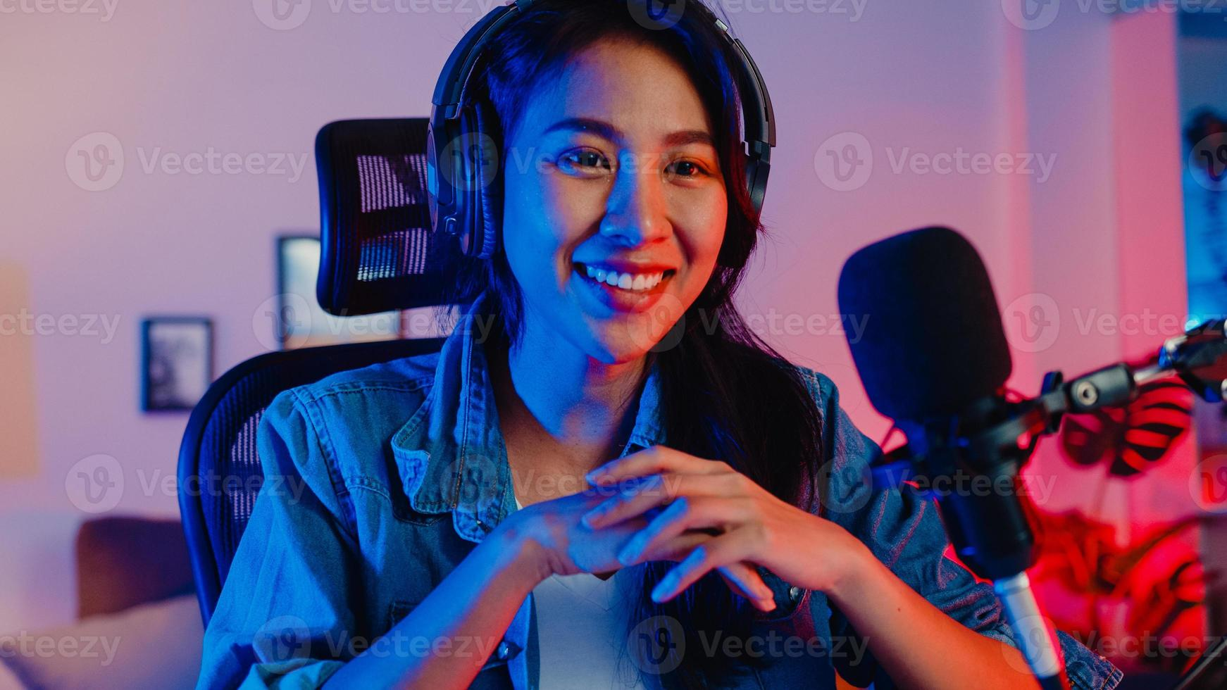 Happy Asia Girl Blogger Music Influencer mit Blick auf die Kamera-Sendungsaufzeichnung tragen Kopfhörer online Live-Gespräch im Mikrofon mit Publikum im Wohnzimmer-Heimstudio in der Nacht. Inhaltsersteller-Konzept. foto