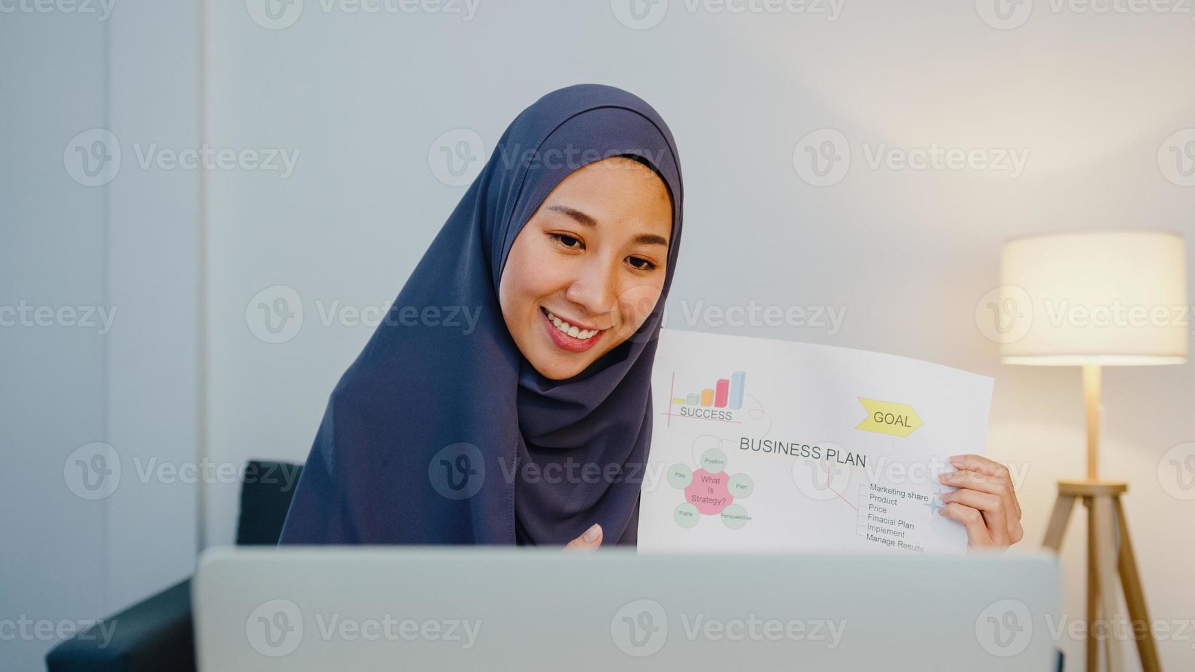 Asiatische muslimische Dame trägt Hijab mit Computer-Laptop Sprechen Sie mit einem Kollegen über den Plan in einem Videoanruf-Meeting, während Sie von zu Hause aus nachts im Wohnzimmer arbeiten. soziale Distanzierung, Quarantäne wegen Corona-Virus. foto