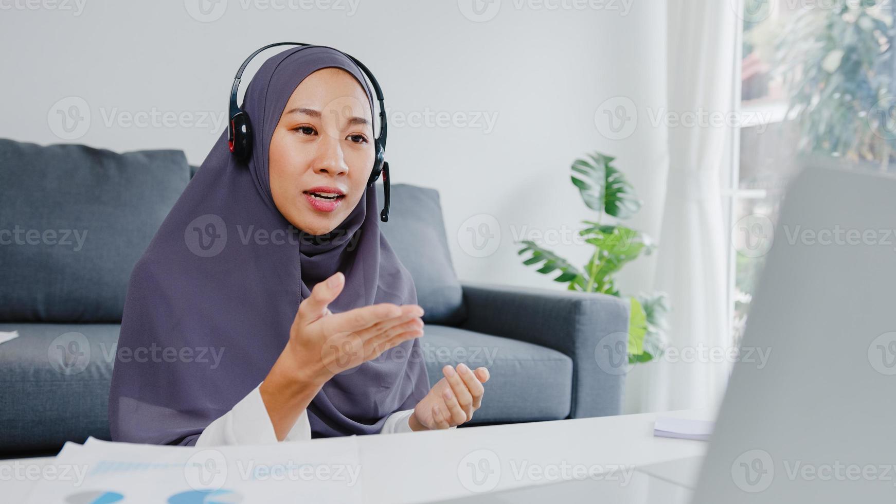 asiatische muslimische dame tragen kopfhörer mit laptop sprechen mit kollegen über den plan in konferenz-videoanrufen, während sie von zu hause im wohnzimmer arbeiten. soziale Distanzierung, Quarantäne zur Vorbeugung des Coronavirus. foto