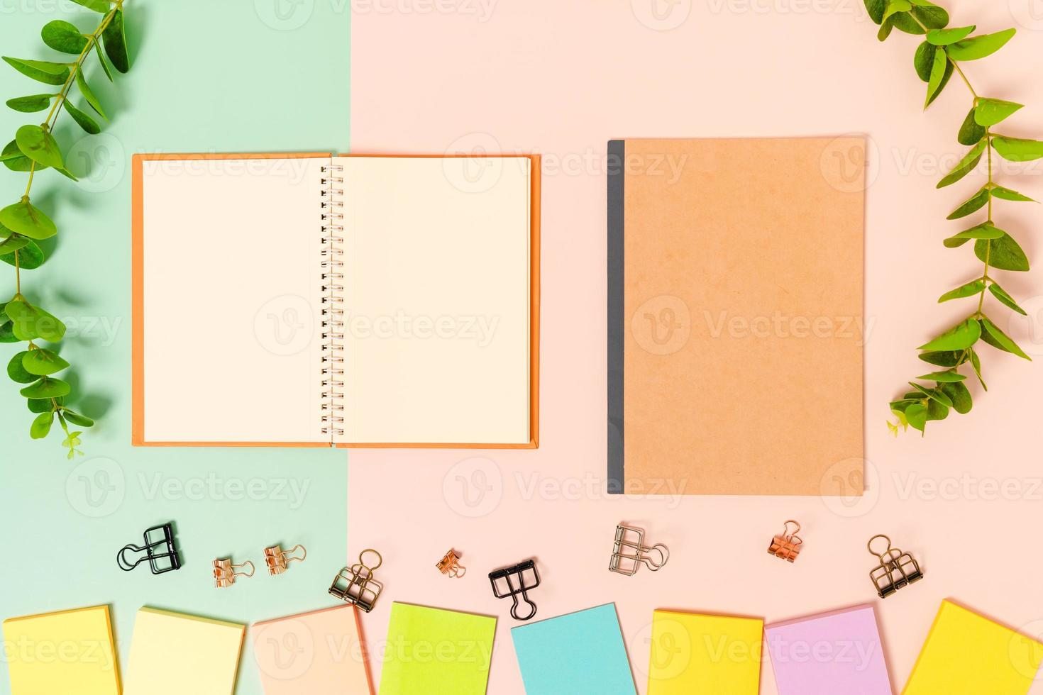 kreatives flaches Laienfoto des Arbeitsplatzschreibtisches. Schreibtisch von oben mit Haftnotiz und offenem schwarzen Notizbuch auf pastellgrünem rosa Hintergrund. Draufsichtmodell mit Kopienraumfotografie. foto