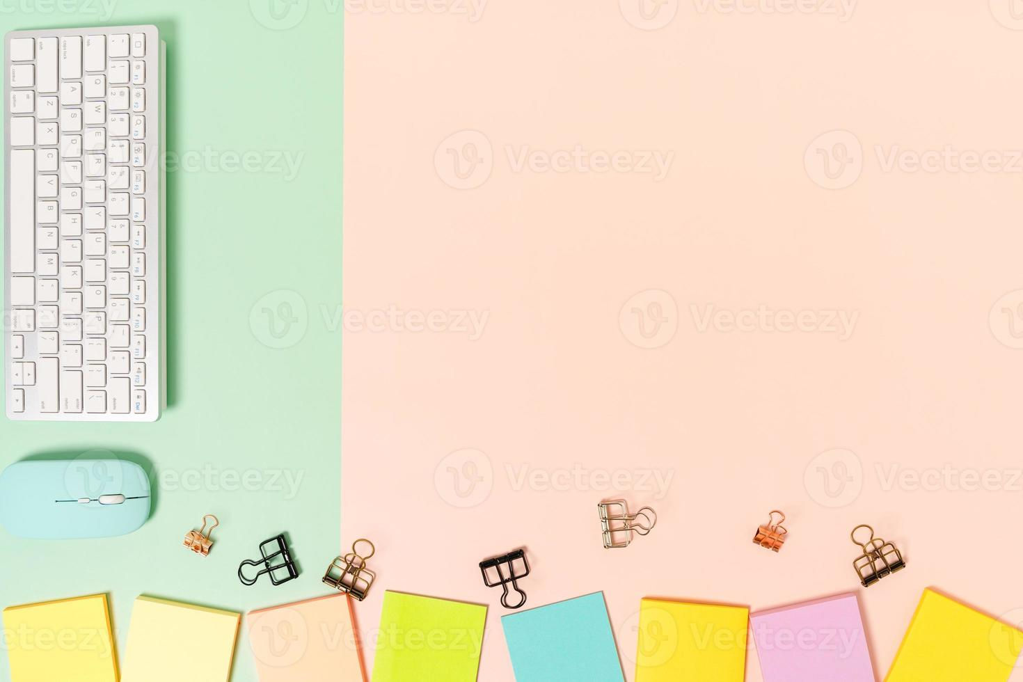 minimaler arbeitsplatz - kreatives flaches foto des arbeitsplatzes. Schreibtisch von oben mit Tastatur, Maus und Klebezettel auf pastellgrünem rosa Hintergrund. Draufsicht mit Kopienraumfotografie.