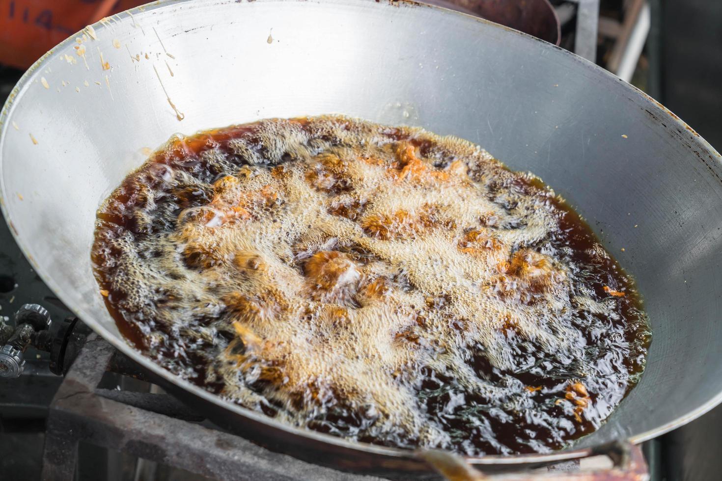gebratenes Hähnchen in Pfanne mit kochendem Öl foto