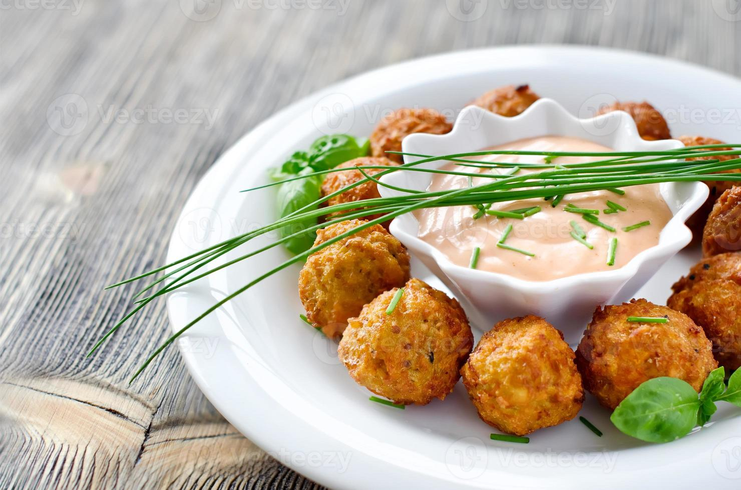Falafels auf einem Teller mit Dip-Sauce und Kräutern foto