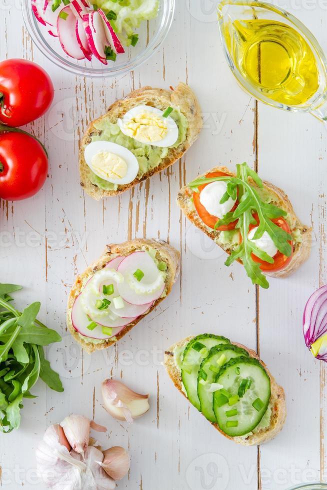 Zubereitung von Sommersandwiches - Brot, Guacamole, Ruccola, Tomaten, Radieschen, Gurke foto