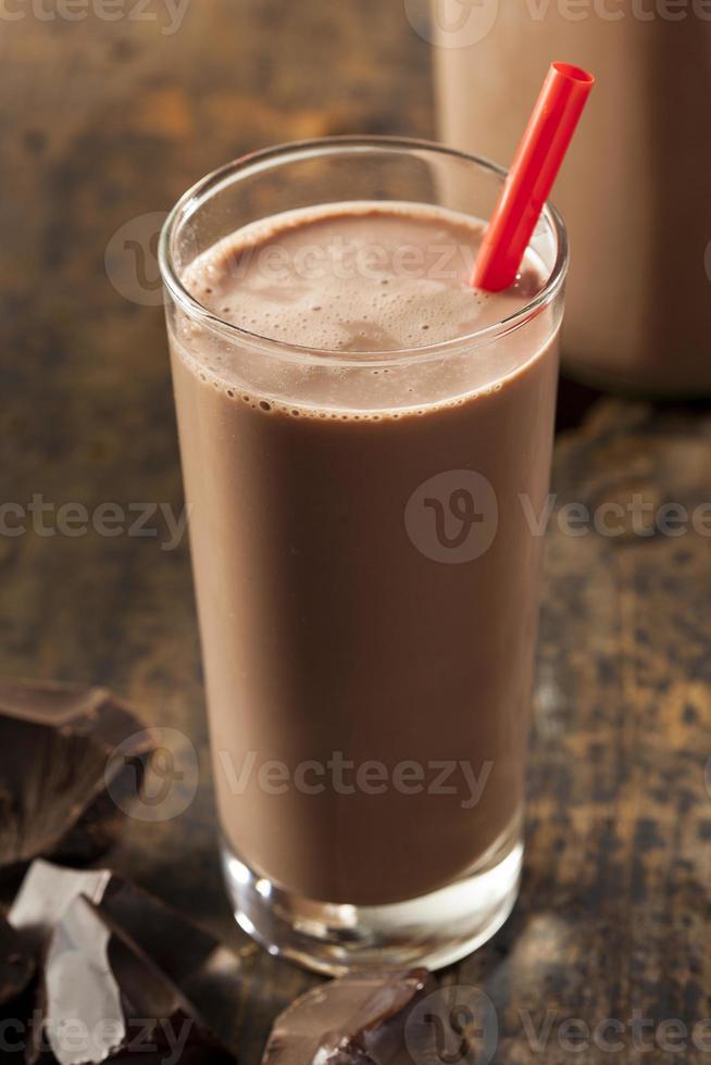 Glas Schokoladenmilch mit rotem Stroh auf einem Holztisch foto