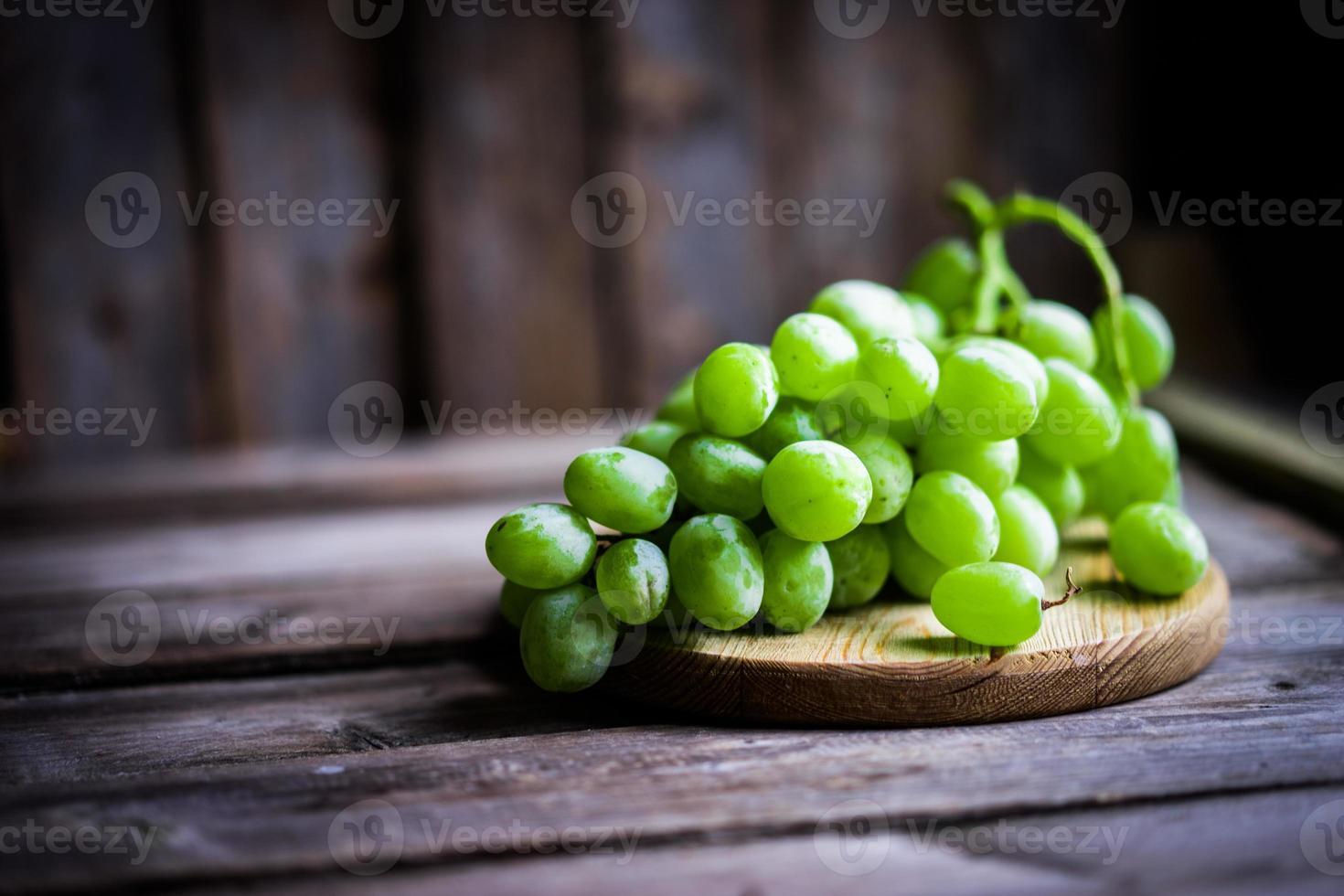Weinrebe der grünen Trauben auf rustikalem hölzernem Hintergrund foto