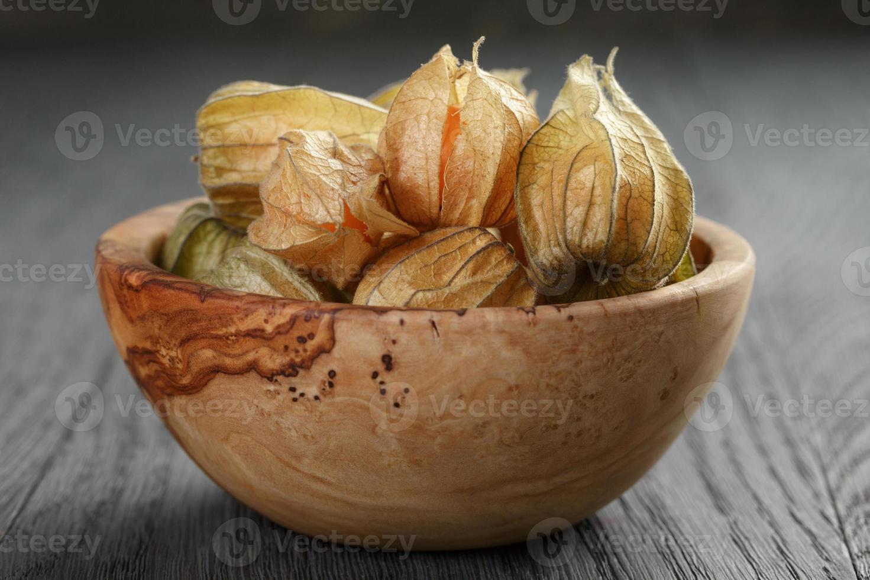 Physalisfrucht in Olivenschale auf Eichenholztisch foto