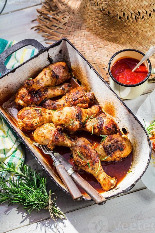 würzige Hähnchenschenkel mit Kräutern und Sauce foto