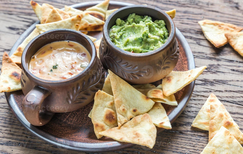 Schalen mit Guacamole und Queso mit Tortillachips foto
