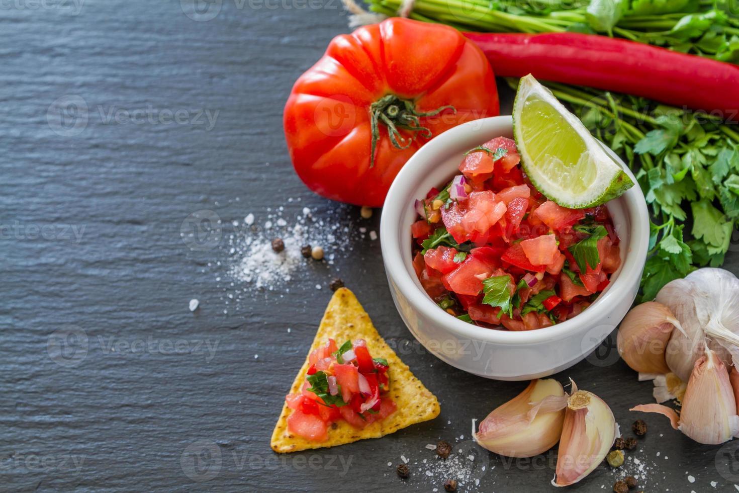 Salsa-Sauce und Zutaten - Tomaten, Zwiebeln, Chili, Knoblauch, Limette foto